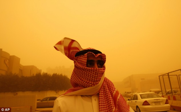 A Saudi covers his face with his traditional headdress as the sandstorm colors the sky.  Source: AP