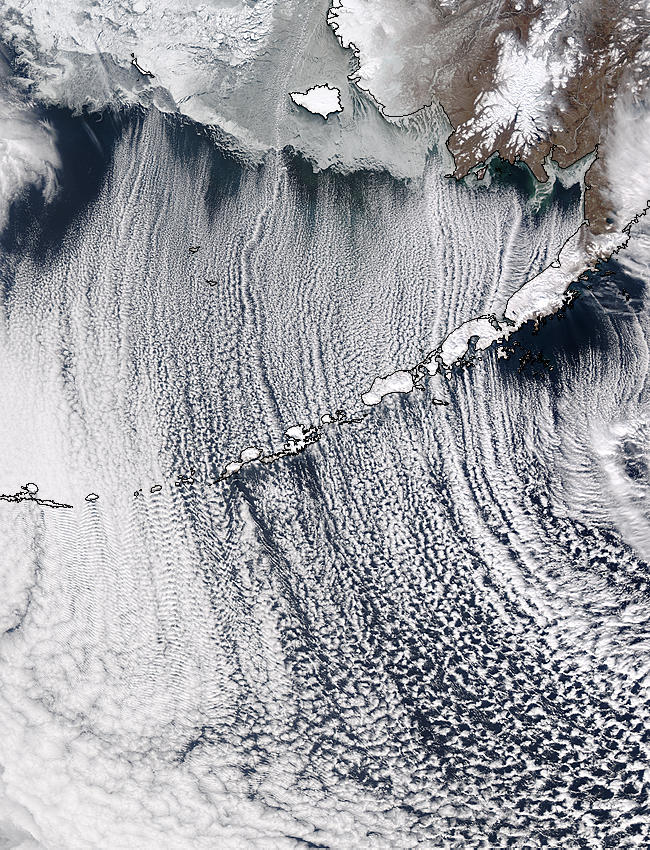 Cloud streets off the coast of Alaska.  As this image displays, cloud streets often form when cold air flows off of a land mass and over warmer ocean waters.  In this image, the wind flow from north to south causes cold air over land to flow over warm ocean waters, generating lift.