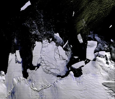 This satellite photograph shows large icebergs calving from the larger antarctic ice sheet at the edge of the south pole.